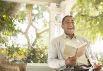 Laughing senior man reading book on porch — Stock Photo