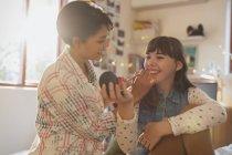 Young women friends applying makeup — Stock Photo