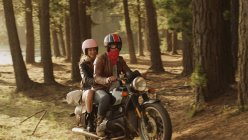 Young couple riding motorcycle in woods — Stock Photo