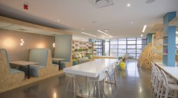Modern, creative shared workspace with table and booths — Stock Photo