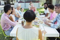 Friends talking at table outdoors — Stockfoto