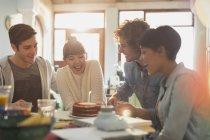 Молодые друзья празднуют день рождения при помощи торта и свечи — стоковое фото