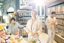 Portrait smiling young woman grocery shopping in market — Stock Photo