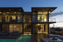 Luxury house with swimming pool illuminated at night — Stock Photo