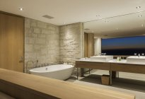 Modern bathroom with soaking tub at night — Stock Photo