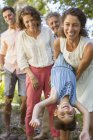 Mother and daughter playing with family outdoors — Stock Photo