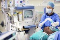 Жінці – лікарю носіння хірургічні одягу знеболюючу пацієнта в операційних театру — стокове фото