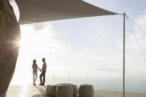 Couple standing on modern balcony — Stock Photo