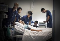 Group of doctors caring for patient in hospital ward — Stock Photo