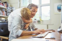 Boy hugging working father — Stock Photo