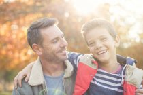 Portrait smiling father and son in front of autumn leaves — Stock Photo
