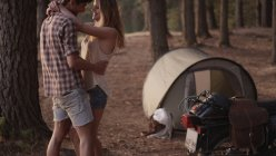 Affectionate young couple hugging outside tent in woods — Stock Photo