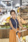 Portrait smiling young woman grocery shopping at market — Stock Photo