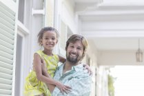 Father holding daughter in arms outdoors — Stockfoto