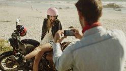 Молодой человек фотографирует женщину на мотоцикле на пляже — стоковое фото