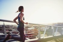 Läuferin läuft auf sonnigem städtischen Steg — Stockfoto