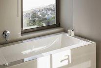 Sunny reflection over modern white bathtub below window — Stock Photo