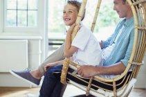 Padre e figlio seduti in poltrona di vimini — Foto stock