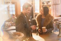 Couple with cell phone and coffee at counter in cafe — Stockfoto