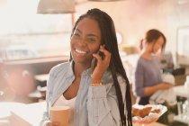 Улыбающаяся женщина разговаривает по телефону и пьет кофе в кафе — стоковое фото