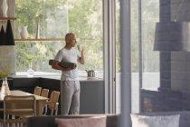 Зріла людина з йога килимок, пити каву кухні — стокове фото