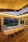 Illuminated slanted wood ceiling over long dining table — Stock Photo