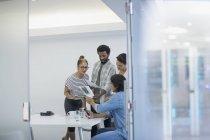 Творческие бизнесмены обсуждают бумажную работу в конференц-зале — стоковое фото