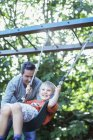 Father pushing son on swing outdoors — Stock Photo