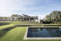 Modern swimming pool, yard and house — Stock Photo