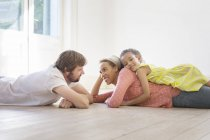 Family laying on the ground together in living space — Stock Photo
