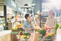 Young women friends with shopping carts talking in grocery store market — Stock Photo