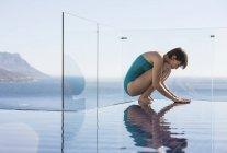 Donna accovacciata sulla piscina a sfioro con vista sull'oceano — Foto stock