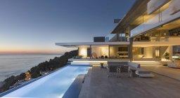 Moderno iluminado, patio exterior de escaparate de la casa de lujo con piscina y el océano se ve en el crepúsculo - foto de stock