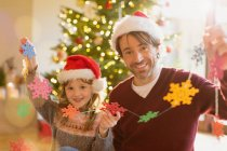 Porträt, Lächeln, Vater und Tochter in Santa Hüte halten Zeichenfolge Papier Schneeflocken — Stockfoto