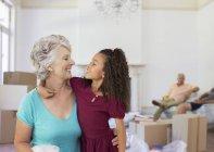 Бабушка и внучка обнимаются в жилом пространстве — стоковое фото