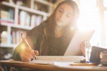 Девочка-подросток с цифровым планшетом делает домашнее задание за солнечным столом — стоковое фото
