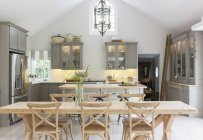 Wooden dining table in luxury kitchen — Stock Photo