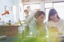 Texto de mujeres jóvenes con teléfono celular en el apartamento - foto de stock