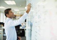 Empresário escrevendo em quadro branco no escritório — Fotografia de Stock