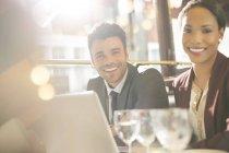 Jóvenes empresarios sonriendo en el restaurante - foto de stock