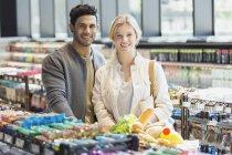 Retrato sonriente compras pareja joven en el mercado - foto de stock