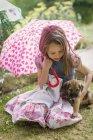 Fille avec chien chiot tenant parapluie en forme de coeur dans l'herbe — Photo de stock