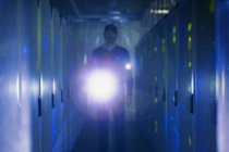 Server room technician with flashlight in dark corridor — Stock Photo