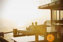 Силует пара розслабляючий на шезлонг лаунж-насолоджуючись видом на захід сонця океан — стокове фото