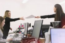Femme d'affaires remettant la paperasse à un collègue sur les ordinateurs dans le bureau — Photo de stock
