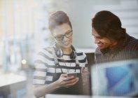 Kreative Geschäftsleute mit Kopfhörern per Smartphone im Büro — Stockfoto