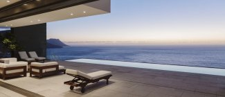 Modern patio and infinity pool overlooking ocean at sunset — Stock Photo