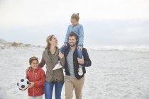 Семья с футбольным мячом прогулка по зимнему пляжу — стоковое фото