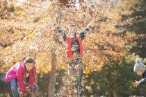 Garotos brincalhões e menina correndo e pulando em folhas de outono — Fotografia de Stock