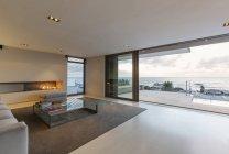 Modernes, minimalistisches Luxus-Wohnzimmer mit Gas-Kamin und Terrassentüren mit Meerblick und Patio — Stockfoto
